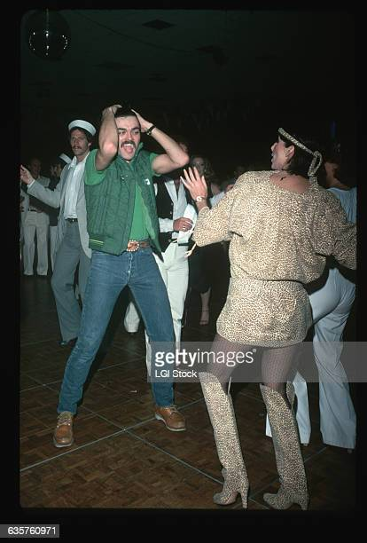 Cher dances with Randy Jones, the Cowboy from the Village People, at a disco.