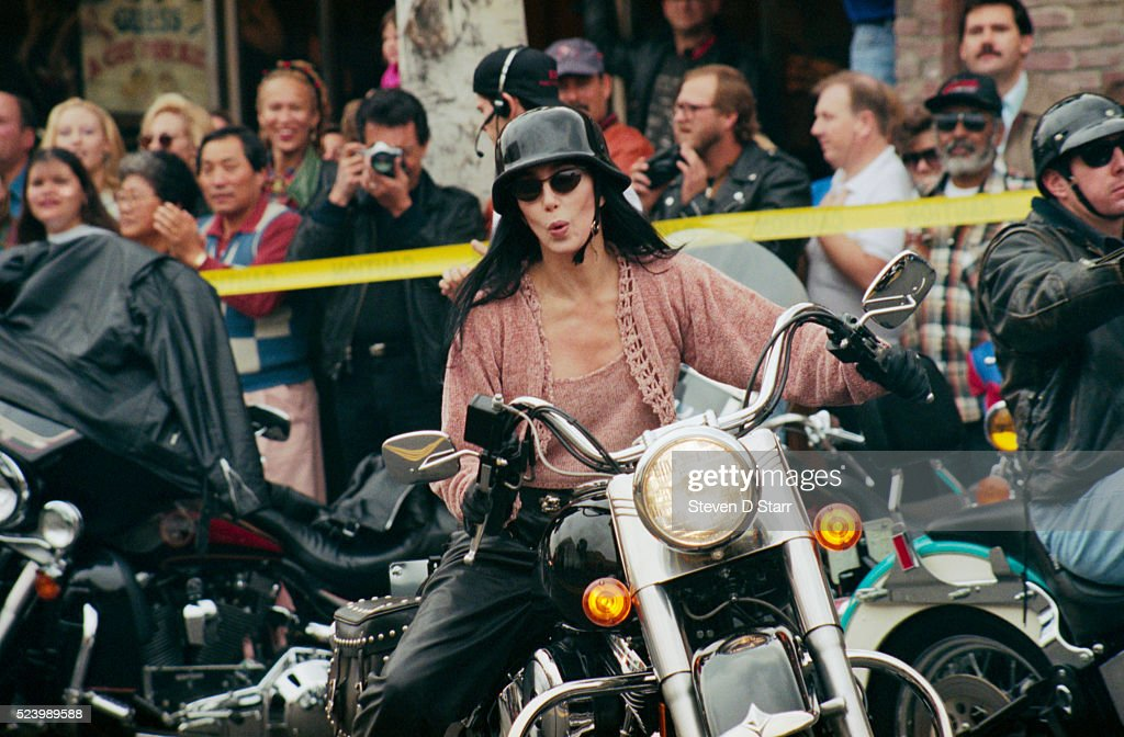 Cher rides a Harley Davidson motorcycle during a Christmas parade on Rodeo Drive.
