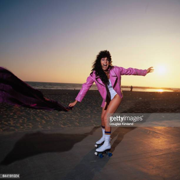 Cher roller skates at Venice Beach wearing a pink leather jacket and white swimsuit
