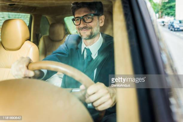 cherful businessman traveling by a car - formal stock pictures, royalty-free photos & images