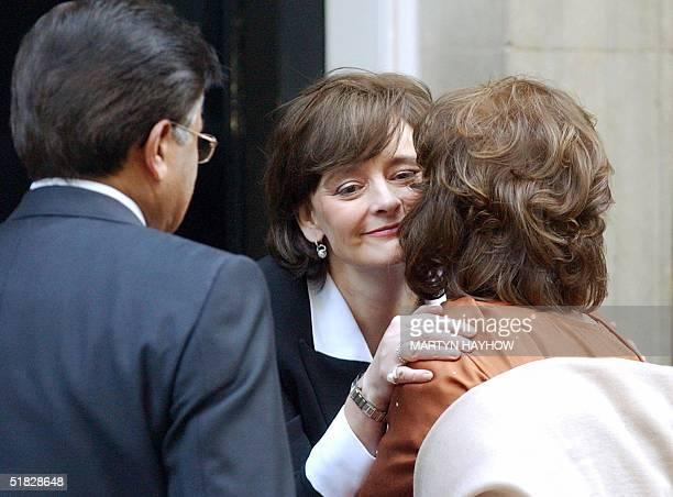 Cherie Blair greets Sehba Musharraf as her husband Pakistani President Pervez Musharraf looks on at No 10 Downing Street in London 06 December 2004...