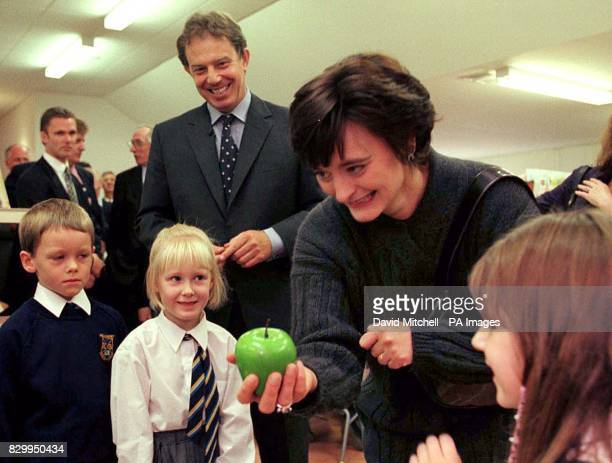 Cherie Blair purchases an apple from Primary 1's shop as her husband Prime Minister Tony Blair looks on during a visit to Killermont Primary School...
