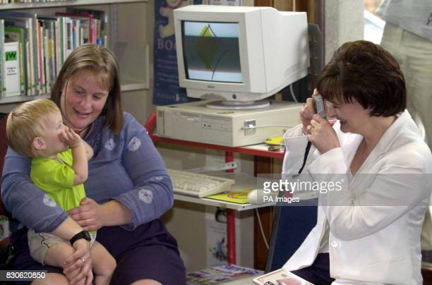 Cherie Blair Wife of Prime Minister Tony Blair takes a photograph of one year old Louie Jones and his mother Lyn Jones at Hangleton Library Essex *Mr...