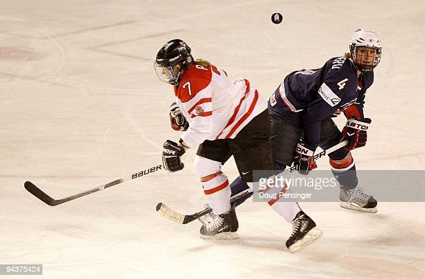 Cherie Piper of Canada battles for the puck with Angela Ruggiero of the USA during their Women's Ice Hockey match at the Magness Arena on the Denver...