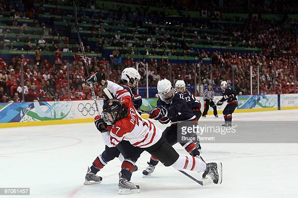 Cherie Piper of Canada is checked by Kerry Weiland of the United States during the ice hockey women's gold medal game between Canada and USA on day...