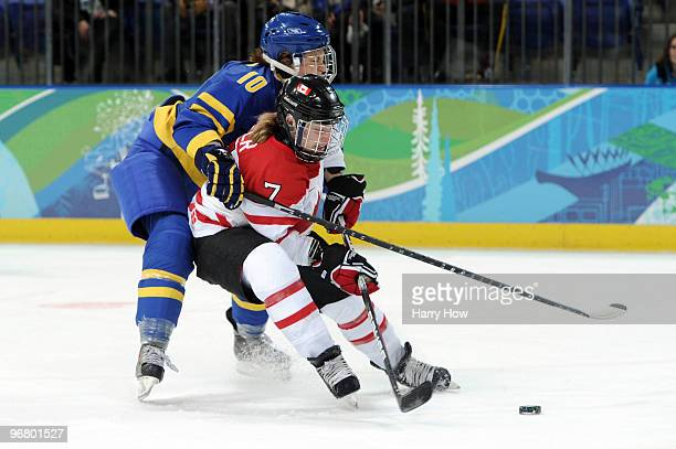 Cherie Piper of Canada scores her team's third goal under pressure from Emilia Andersson of Sweden during the ice hockey women's preliminary game...