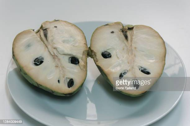 cherimoya fruit in halves n a white plate - dorte fjalland stock pictures, royalty-free photos & images
