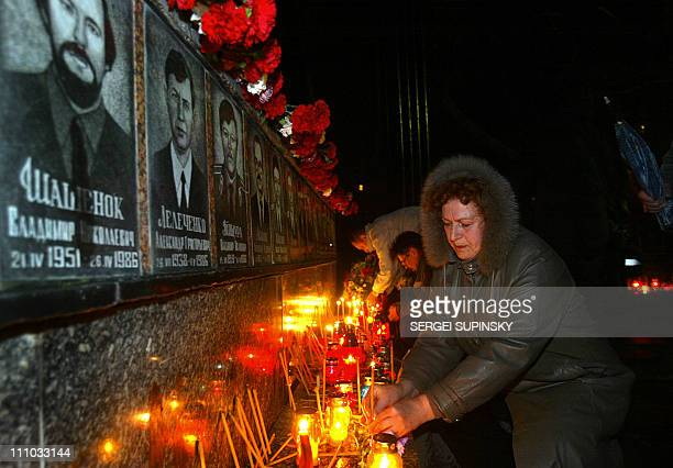 A Chernobyl widow sets a candle on the gravestone of firemen at Memorial to Chernobyl victims in Slavutich a small town were workers at the plant...