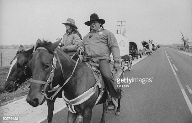 Cherokee indian Archie Mouse riding horse w woman at front of horsedrawn covered wagon train reenacting 1000mile journey that Cherokees traveled...