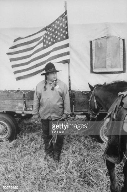 Cherokee indian Archie Mouse standing in front of American flag and covered wagon which he is using to reenact the 1000 mile journey that his...