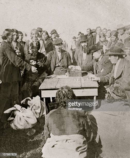 Cherokee payments Several men seated around table counting coins large group of Native Americans stand in background 1880