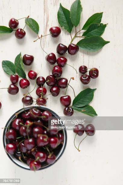 Cherries and bowl on white wooden table