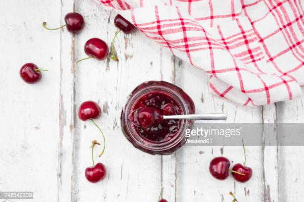 cherries beside open jar of cherry jam on white wood - dish towel stock pictures, royalty-free photos & images