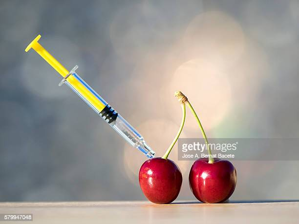 Cherries with a syringe stuck concept of genetically modified foods or GMOs