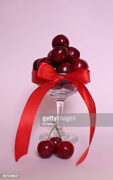 cherries wrapped in a red bow - cherry kiss photos et images de collection
