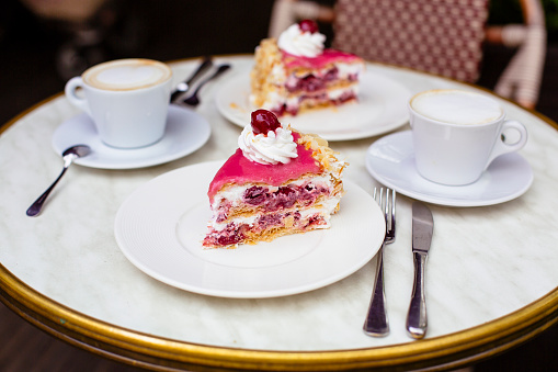 Cherry cake and cappuccino on the table in a cafe - gettyimageskorea