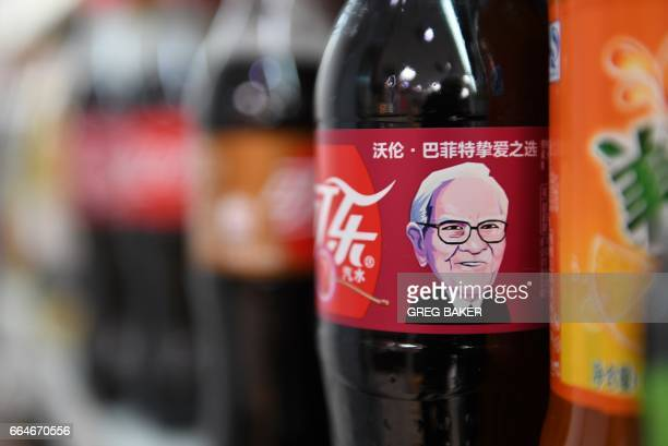 A Cherry Coke bottle featuring an image of US investor Warren Buffet is seen on a shelf at a convenience store in Beijing on April 5 2017 The...
