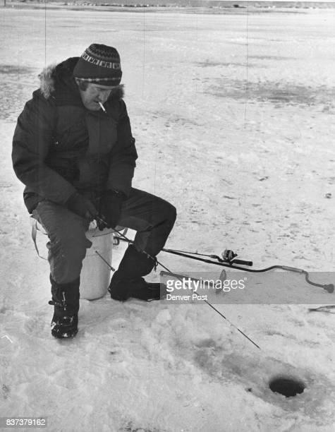 A cherry creek ice angling expert and the tools of the trade Don Murphy using bucket for chair holds superlight rod On ground are auger ice scooper...