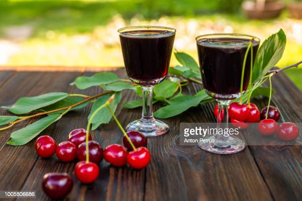 cherry liqueur and fresh cherries on a wooden background - liqueur stock pictures, royalty-free photos & images