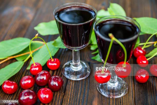 Cherry liqueur and fresh cherries on a wooden background