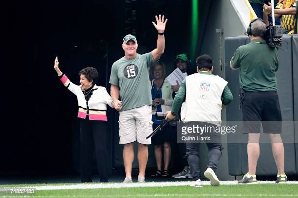 Cherry Louise Morton, wife of Bart Starr, and Brett Favre wave to the crowd before the game between the Minnesota Vikings and Green Bay Packers at...