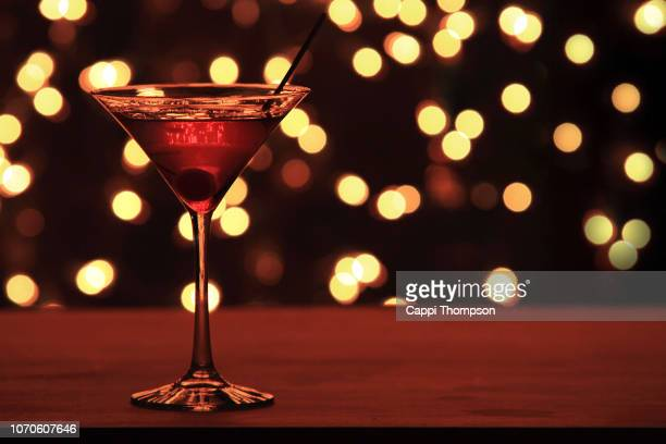cherry martini on bar counter - martini glass stock pictures, royalty-free photos & images