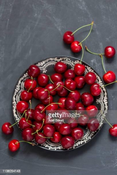 cherry on black background - サワーチェリー ストックフォトと画像