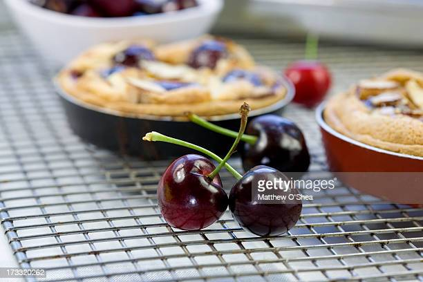 Cherry pie cooling on a rack with fresh cherries
