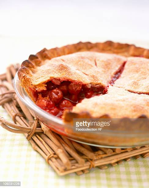 Cherry pie with slice removed in baking dish, close-up
