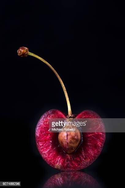 cherry sliced in half with black background - cherry stock pictures, royalty-free photos & images