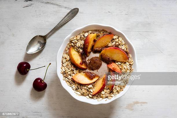 Cherry smoothie bowl with peach and oat flakes, topping