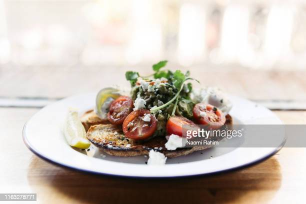 cherry tomato and smashed avocado bruschetta, served on toasted sourdough bread on a timber table - avocado toast stockfoto's en -beelden
