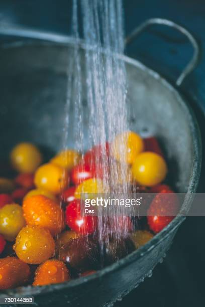 Cherry tomatoes in a colander under running water