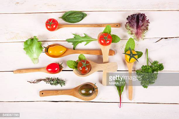 Cherry tomatoes, lettuce and herbs on wooden spoon