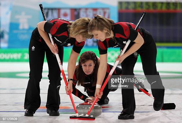 Cheryl Bernard of Canada releases a stone as Carolyn Darbyshire and Cori Bartel sweep the ice during the women's gold medal curling game between...