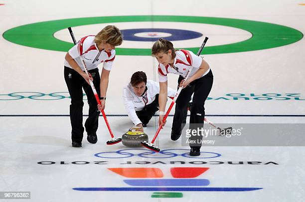 Cheryl Bernard of Canada releases the stone as teammates Carolyn Darbyshire and Cori Bartel brush the ice during the Women's Curling Round Robin...