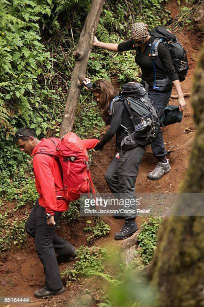 Cheryl Cole and Alesha Dixon are helped down down a ravine by a guide on the first day of The BT Red Nose Climb of Kilimanjaro on February 1 2009 in...