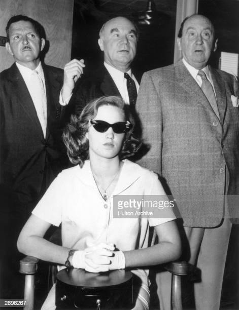 Cheryl Crane daughter of actor Lana Turner sits in a chair with her hands folded in her lap wearing dark sunglasses while three unidentified men...