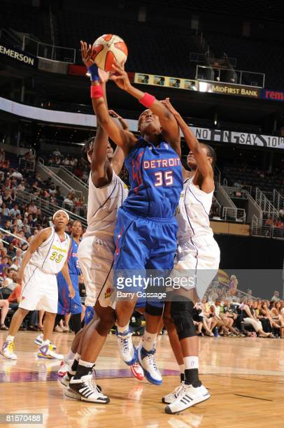 Cheryl Ford of the Detroit Shock shoots against Barbara Farris and LaToya Pringle of the Phoenix Mercury on June 14 at US Airways Center in Phoenix...