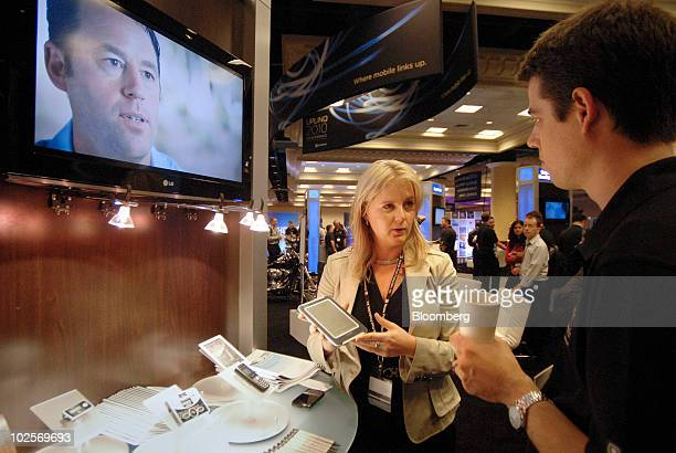 Cheryl Goodman a marketing director for Qualcomm Inc demonstrates a 57 inch Qualcomm Mirasol eink reflective display to Chris Gould at the Uplinq...