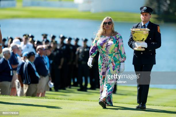 Cheryl Lee widow of Fire Captian Mark Lee Sr of Engine Company 10 and son Mark Lee junior carry the President's Cup trophy during the first round of...
