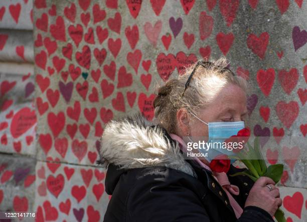 Cheryl Mayne smells tulips that she then leaves next to a heart she drew in memory of her brother Mark Sarnham who died from Covid-19 at the Covid-19...