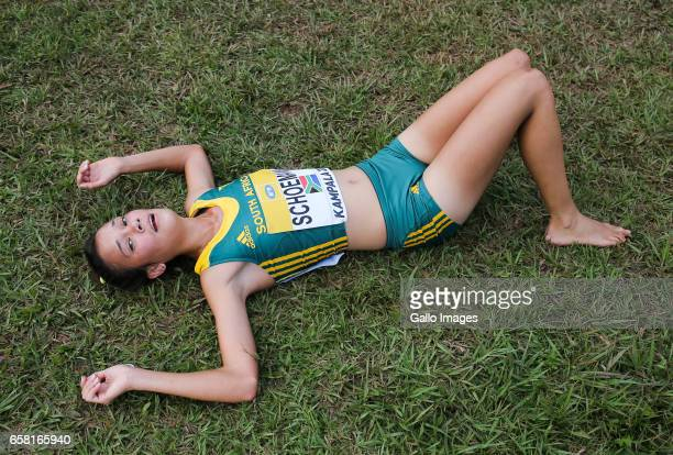 CheryLee Schoeman of South Africa lies exhausted at the finish line during the U20 women race of the 2017 Kampala IAAF World Cross Country...