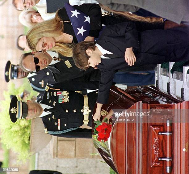 Chesare Bono places a rose on the casket of his father Sonny Bono as his mother Mary Bono holds the US flag during the burial ceremony of the...