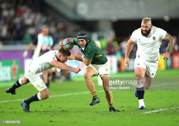 Cheslin Kolbe of South Africa breaks through the tackle of Owen Farrell of England to score his team's second try during the Rugby World Cup 2019...