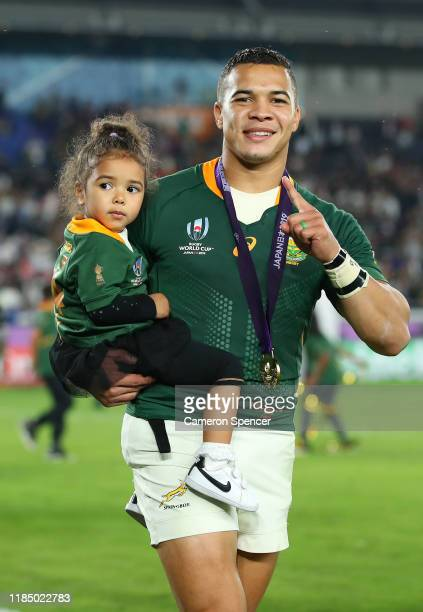Cheslin Kolbe of South Africa celebrates as he carries his daughter Kylah on the pitch after his team's victory against England in the Rugby World...