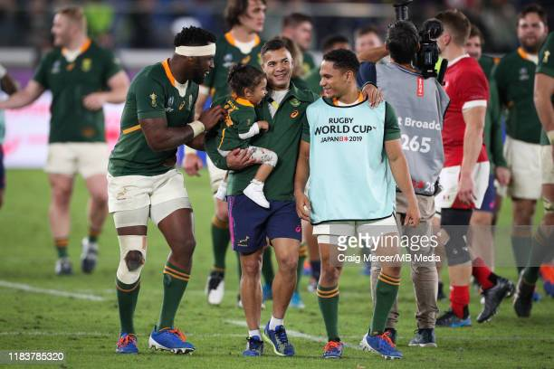 Cheslin Kolbe of South Africa enjoys the victory lap with his daughter and team mates Siya Kolisi and Herschel Jantjies after the Rugby World Cup...