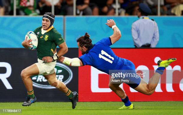 Cheslin Kolbe of South Africa is challenged by Michele Campagnaro of Italy on his way to scoring his team's third try during the Rugby World Cup 2019...