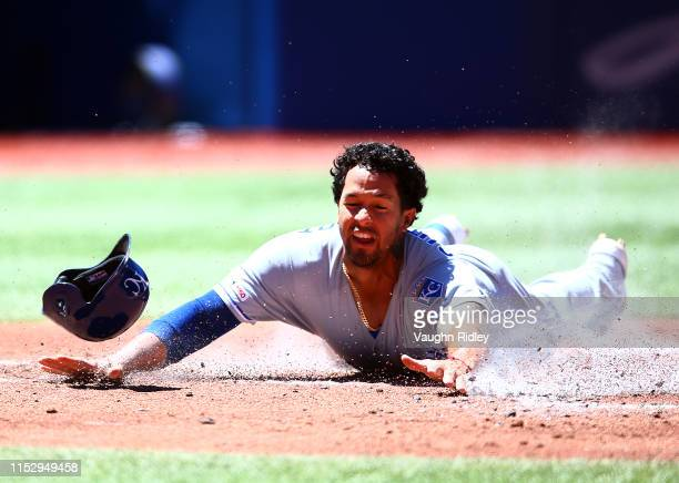 Cheslor Cuthbert of the Kansas City Royals beats the tag at home plate to score a run in the first inning during a MLB game against the Toronto Blue...
