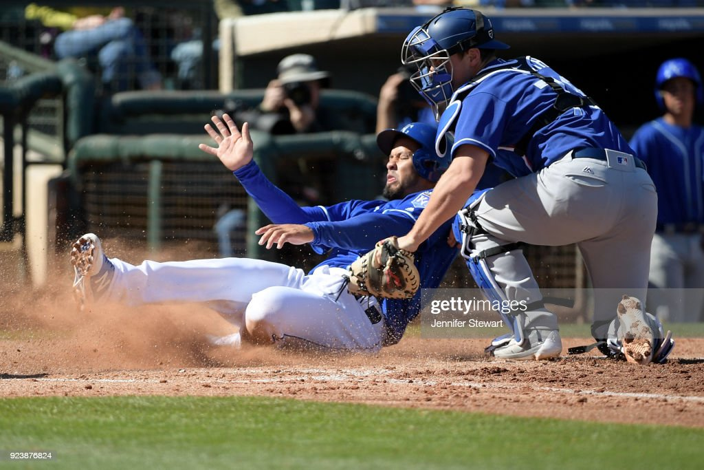 Cheslor Cuthbert #19 of the Kansas City Royals is tagged out at home by Will Smith #79 of the Los Angeles Dodgers at Surprise Stadium on February 24, 2018 in Surprise, Arizona.